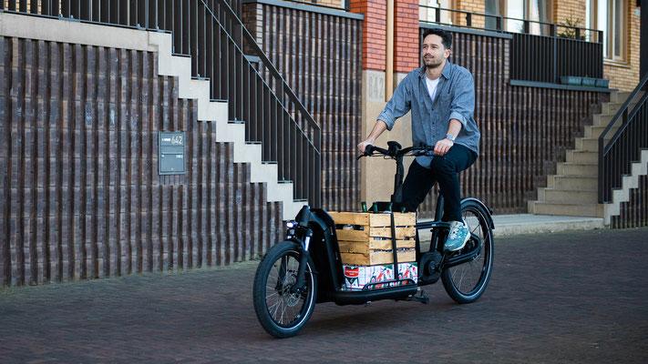 Mann fährt mit dem Lastenrad von Carqon Gegenstände durch die Stadt