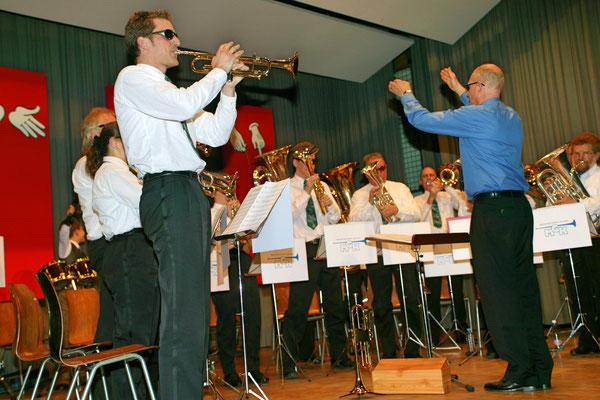 """Jahreskonzert 19. März 2005; Hansjörg Ammann 20 Jahre MGK-Dirigent; links Daniel Widmer """"Everbody needs somebody"""""""
