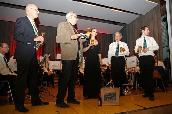 Sepp Ottiger erhält als Geschenk eine Feuerschale, symbolisch dafür Anfeuerholz (Tragtasche); und vom MVU einen Kasten seines Lieblingsbiers; Jubiläumskonzert «125 Jahre MGK» 02.04.2016 MGK und MVU (D); Foto: Ruedi Hunziker, Atelier Lightning, Kölliken