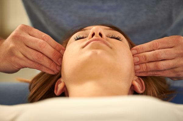 Cranio-sacrale Osteopathie: Behandlung am Kopf einer Frau
