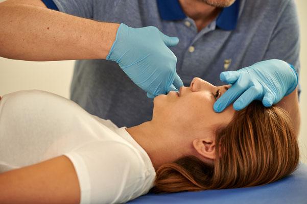 CMD: Behandlung mit Handschuhen am Kiefer einer Frau