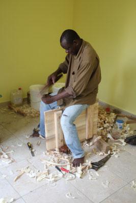 Soumagbo Amevi, der Schreiner passt eine Kastenzüre zum Wandschrank an.