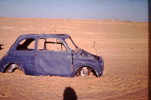 18. Dieser ausgeschlachtete Fiat 500 hat es nicht geschafft bis zur Grenzstadt Ain Guezzam. Ich habe mich insgesammt 3 mal  darauf verewigt. Beim 4. Mal fand ich in nicht mehr. Ob er einfach nur durch  Sandstürme zugedeckt war, oder er dem Strassenbau im
