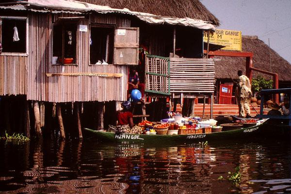 37. Schwimmender Markt in Ganvie. Sie verkauft Gemüse.