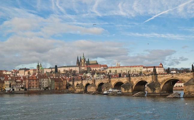Вид на Пражский Град и Карлов мост. В небе живописные свежие и рассеявшиеся химтрейлы