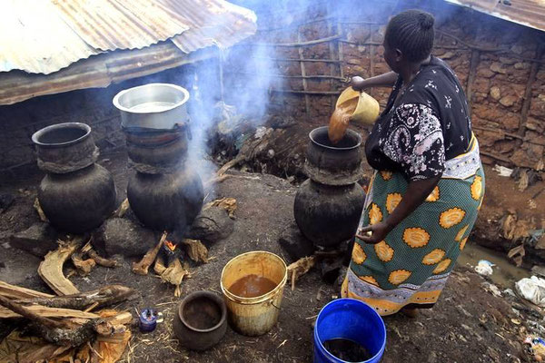 """Una donna impegnata nella preparazione del """"chang'aa"""" a Kibera (Nairobi)"""