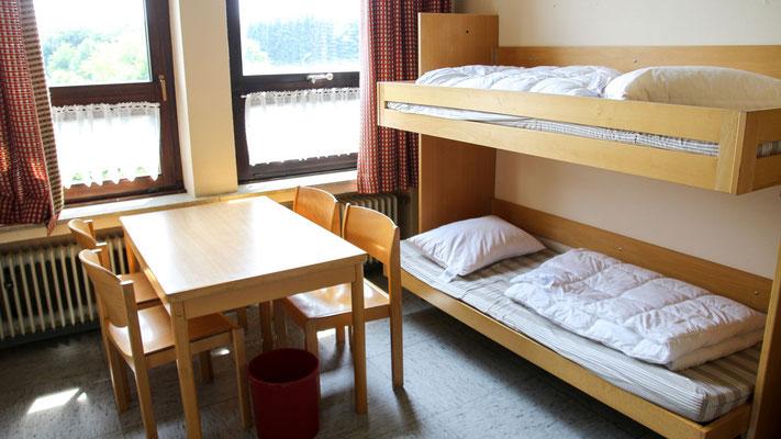 """Neben den vier 8ter-Zimmern befinden sich zwei 4er Zimmer im Erdgeschoss. Eins davon ist direkt an die Küche angebunden, verfügt über ein eigenes WC/Dusche, und eignet sich somit perfekt für das """"Küchenpersonal""""."""
