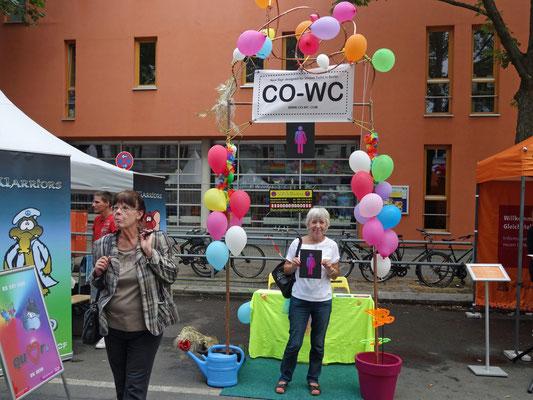 Mensch vor CO-WC Informationsstand beim Lesbisch-schwulen Stadtfest Berlin