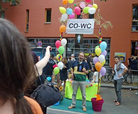 Person zeigt auf CO-WC auf Lesbisch-schwules Stadtfest