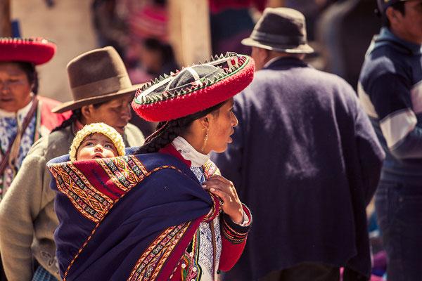 Eine traditionell gekleidete Frau mit Kind auf dem Rücken I Bolivien