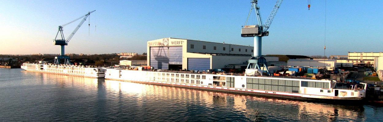 Abbildung 4: Neptun Werft, Blick auf die Schiffbauhalle mit davor liegenden weitgehend fertigen Kreuzfahrtschiffen (Quelle Neptunwerft)