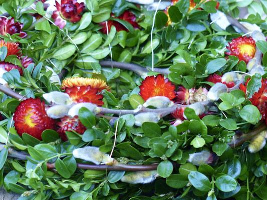 Buchsbaumkranz mit Weidenkätzchen und leuchtend roten Strohblumen