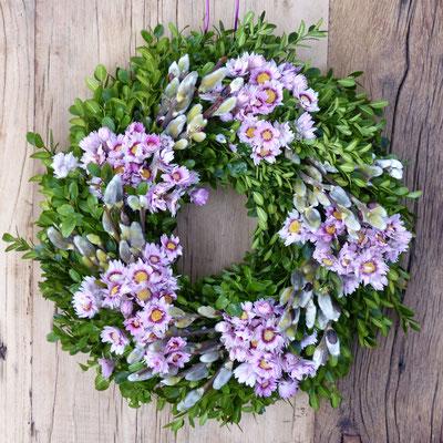 Buchsbaumkranz mit Weidenkätzchen und hellrosanen Rhodantheblüten