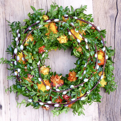 Buchsbaumkranz mit Weidenkätzchen und orangenen Strohblumen