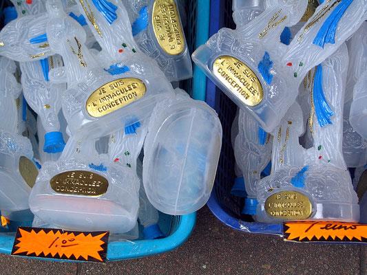 Récipients destinés à recueillir l'eau de la grotte à Lourdes - Les marchands s'enrichissent grâce à Babylone la grande. La France compte plus de 40'000 bâtiments religieux.