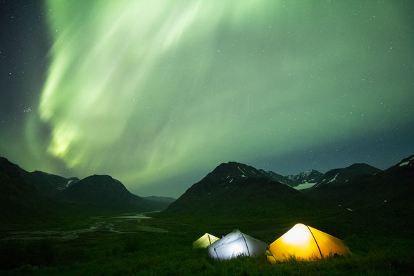 The aurora glowing overhead whilst camping in the Rapa valley of Sarek national Park, Swedish Lapland.