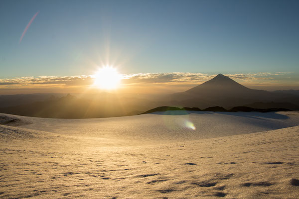 Sunrise over the snow-filled summit crater of Volcan Quetrupillan, Chilean Patagonia.