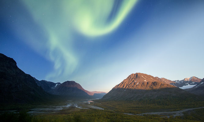 A photo blend of evening light and the aurora glowing above the Rapa valley in Sarek national park, Swedish Lapland.