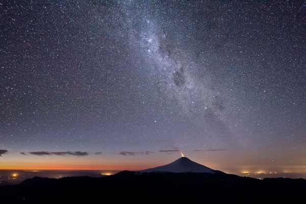 Stars arc over the partially erupting Volcan Villarica, one of South America's most active volcanoes.