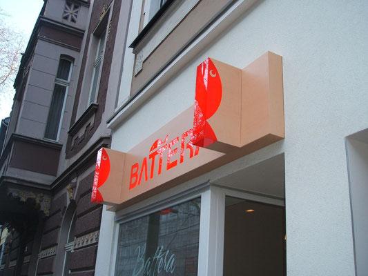 Battera, Düsseldorf | Leuchtkasten mit integrierten Auslegern und Optik in Holzmaserung
