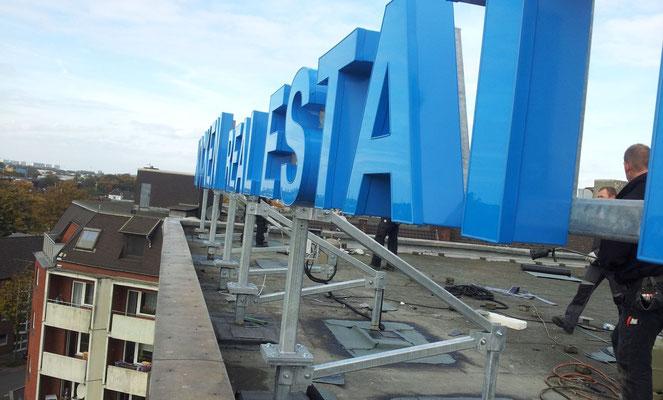 Frank Kocken Immobilien | Einzelbuchstaben im Profil 5 als Dachanlage auf Stahlkonstruktion