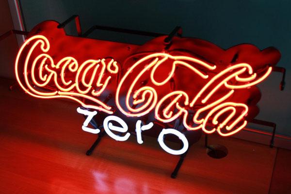 CocaCola - NeonSign mit klarem Neonglas und rotem Leuchtstoff sowie weißem Neonglas auf Gitterrahmen in schwarz