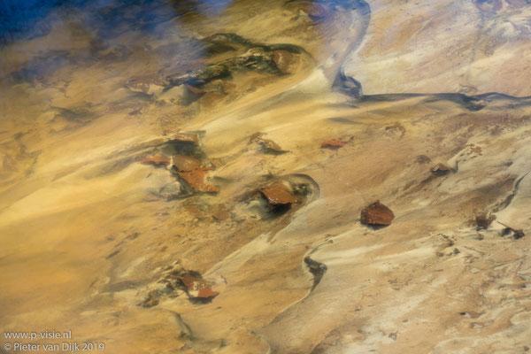 Bladen en zand in de beek