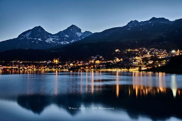 St. Moritz bei Abenddämmerung, Blick auf St. Moritzersee, Lichter von St. Moritz Dorf und die Berge mit Piz Julier und Piz Nair