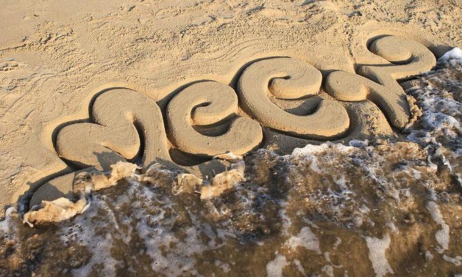 Sandkunst Schriftzug der vom Meer weggespült wird
