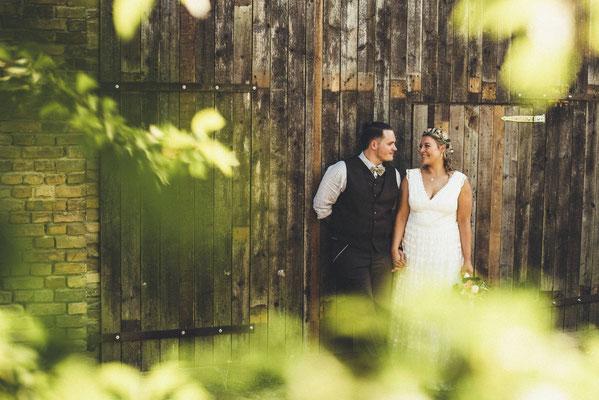 Brautpaar vor der Hochzeitsscheune