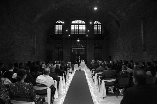 Die Braut schreiten über einen roten Teppich, der mit Lichterketten anstatt Blütenblättern gesäumt ist