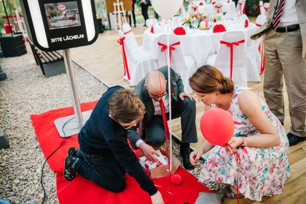 die Hochzeitsplanerin und der Trauzeuge kümmern sich um die Heliumballons