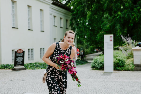 Die Hochzeitsplanerin Stefanie wartet gespannt auf die Braut, um ihr den Brautstrauß geben zu können.