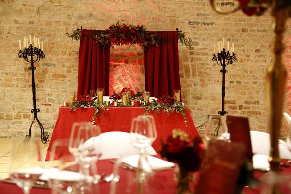 der Brauttisch passt perfekt zur Gesamtdeko - der Traubogen rundet den romantischen Look perfekt ab