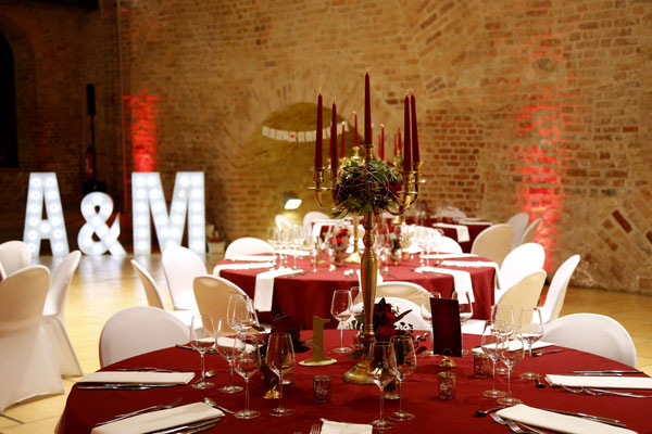 die festlichen runden Tische sind mit bordeaux farbenen Tischdecken eingedeckt