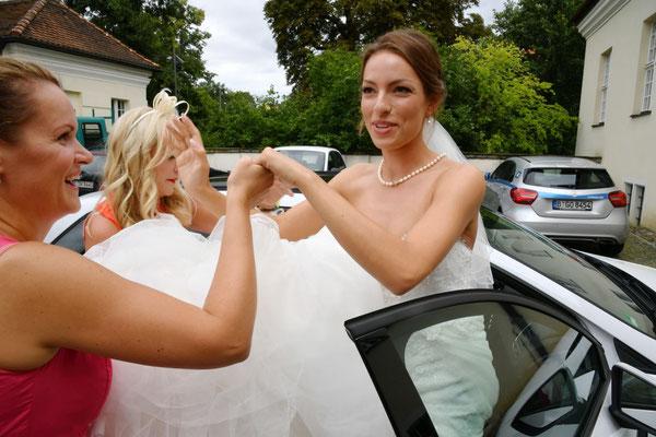 die Hochzeitsplanerin hilft der Braut aus dem Auto