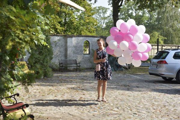 die Hochzeitsplanerin bringt die Heliumballons zu den Gästen, damit diese in den Himmel geschickt werden können