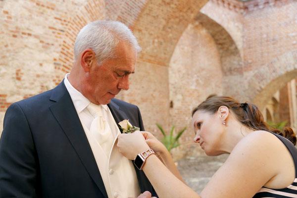 Die Hochzeitsplanerin Stefanie bringt dem Bräutigam seinen Anstecker.