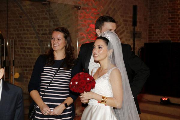 Braut und Hochzeitsplanerin erfreuen sich über die Hochzeitsdekoration im Festsaal