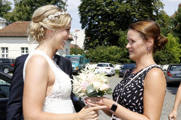 Die hochzeitsplanerin übergibt den Brautstrauß an die Braut