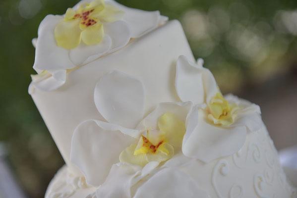 die Hochzeitstorte greift die gelb-weißen Orchideen aus dem Brautstrauß auf
