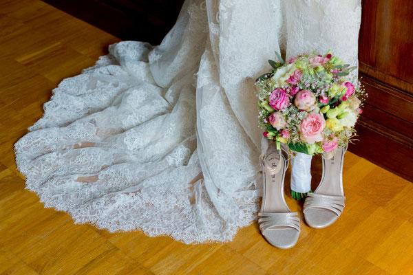 romantisches Brautkleid mit viel Spitze und passendem Brautstrauß