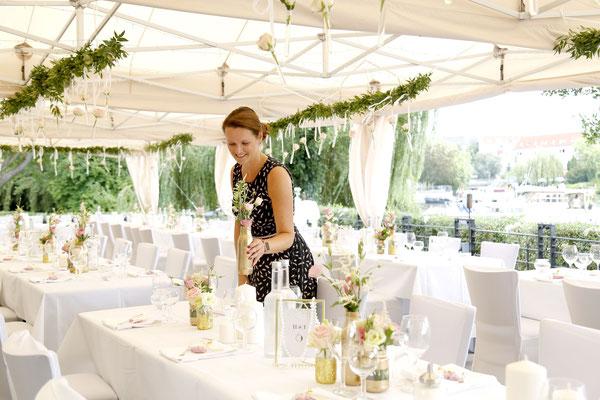 Die Hochzeitsplanerin dekoriert die Festtafeln