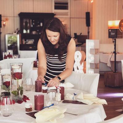 Die Hochzeitsplanerin Stefanie dekoriert währenddessen des Festsaal