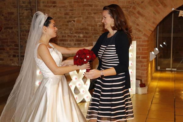 Die Hochzeitsplanerin Stefanie Frädrich übergibt den Brautstrauß an die Braut
