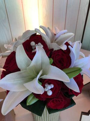 Ein passender Brautstrauß mit roten Rosen und weißen Lilien