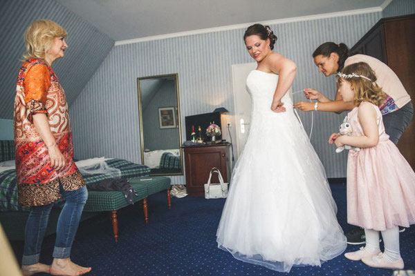 Weddingplaner hilf der Braut ins Kleid