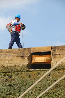 Arbeiter werfen dünne Leinen an Bord und ziehen dann die angeknoteten, dicken Festmacherleinen hoch und belegen diese an Pollern
