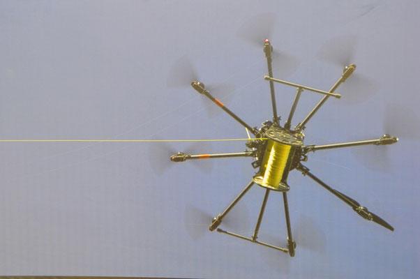 Seilbahnkabel werden mit Hilfe eines Octocopters und einer Holeleine eingeführt.