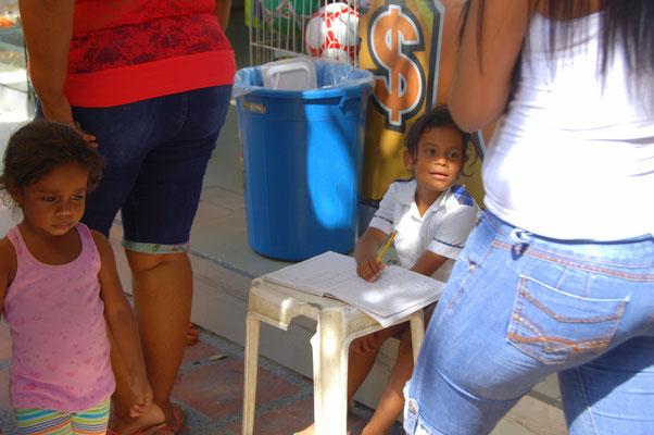 Schulaufgaben auf dem Gehweg, vor dem Laden der Mutter